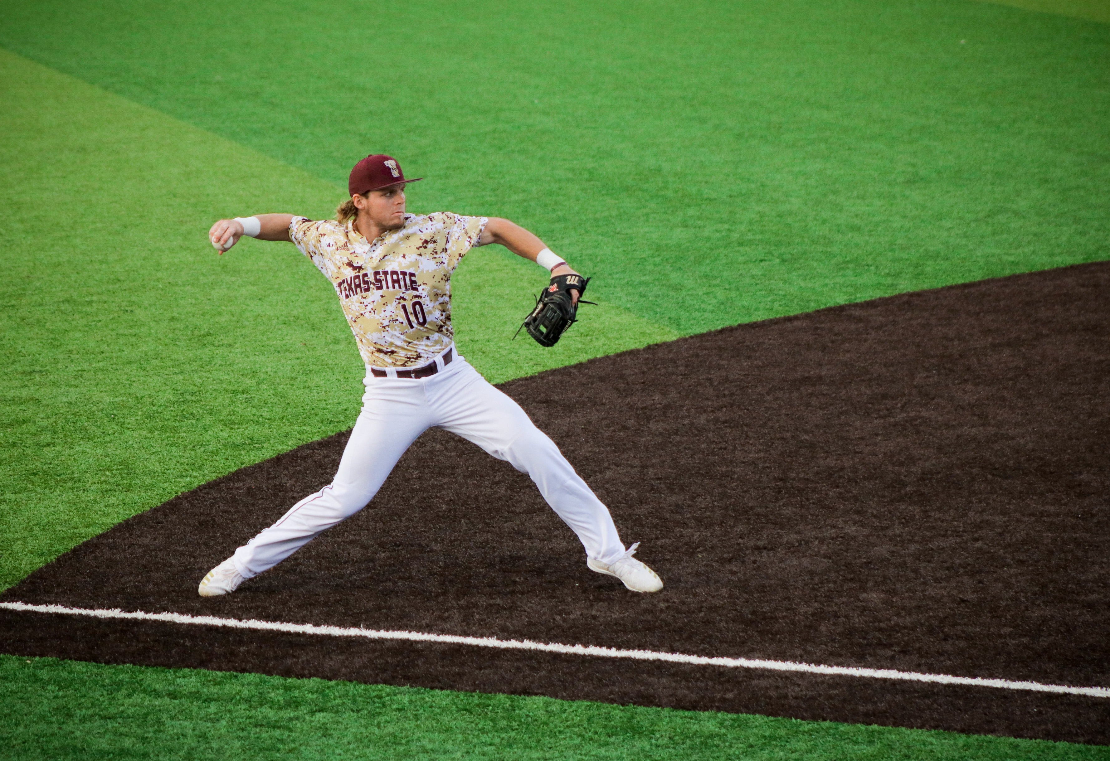 Texas State Bobcat infielder Justin Thompson in a maroon, white and gold digital camo uniform throwing a baseball while at third base at Bobcat Ballpark in San Marcos, TX