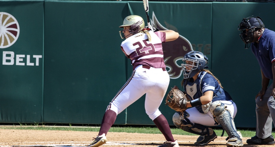 MacKay is up to bat wearing her maroon and white uniform with her gold helmet seconds away from swinging her bat