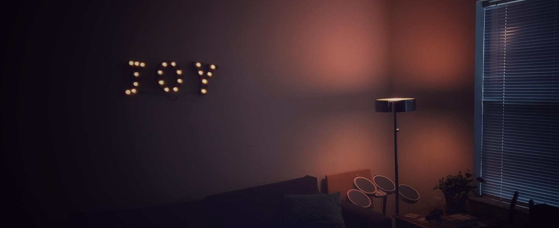 dark room lit up by a dim lamp and the word joy splt out on the wall wuth neon lights.