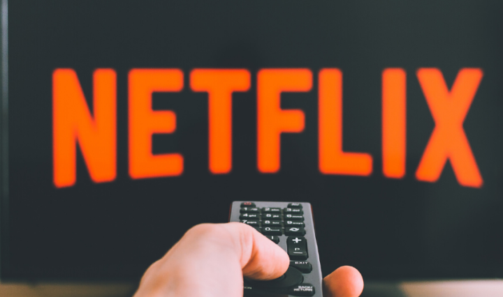 "A hand holding a remote pointing at a TV screen that has the red ""Netflix"" logo"