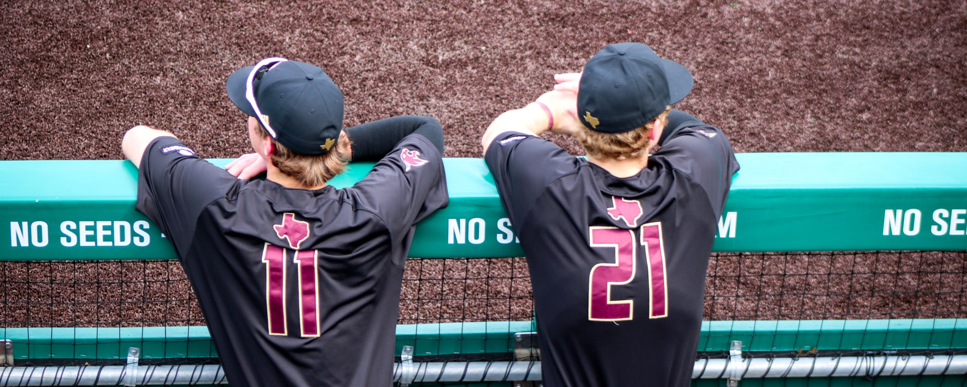 Texas State baseball players in black uniforms lean against the railing of the dugout in Bobcat Ballpark.