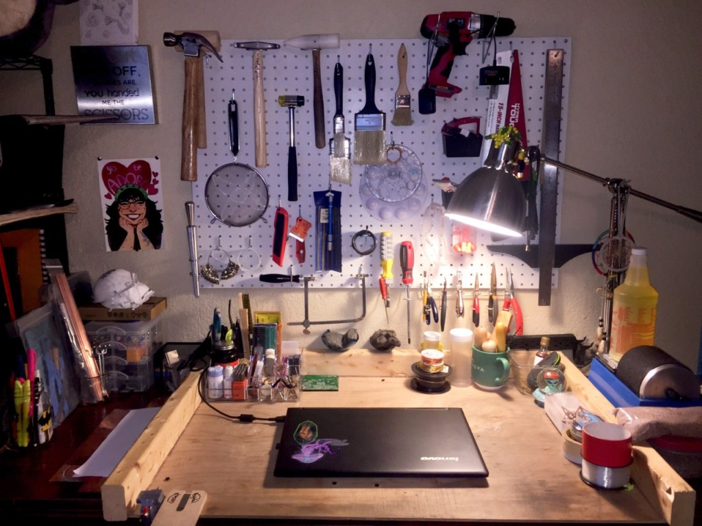 An at-home studio workspace with a mixed arrangement of multi-use tools on a wall and table.