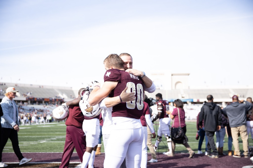 Coach Spavital and senior Hutch White are hugging in the endzone with some fans and other players behind them.