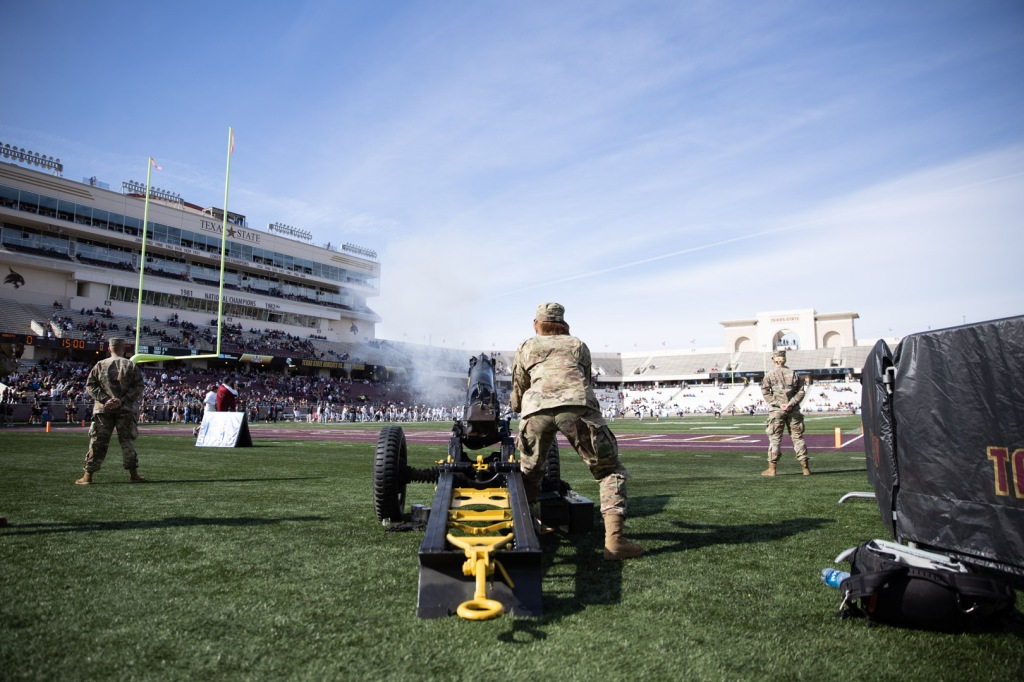 A military cannon is placed beyond the edge of the endzone and field goal while a member of Texas State ROTC operates the machine. Smoke is drifting away from the cannon signifying that the cannon was just used before kickoff.
