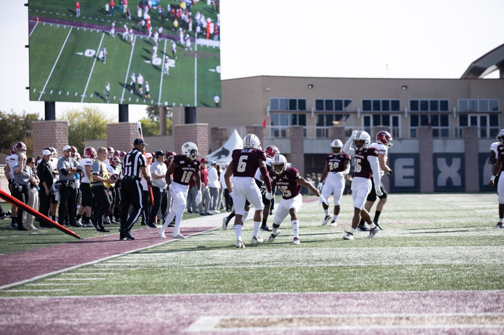 Anthony J. Taylor and Jarron Morris are about to high five near the sideline after a big play.