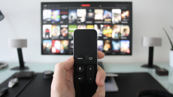 A TV remote in front of a TV screen held by a hand