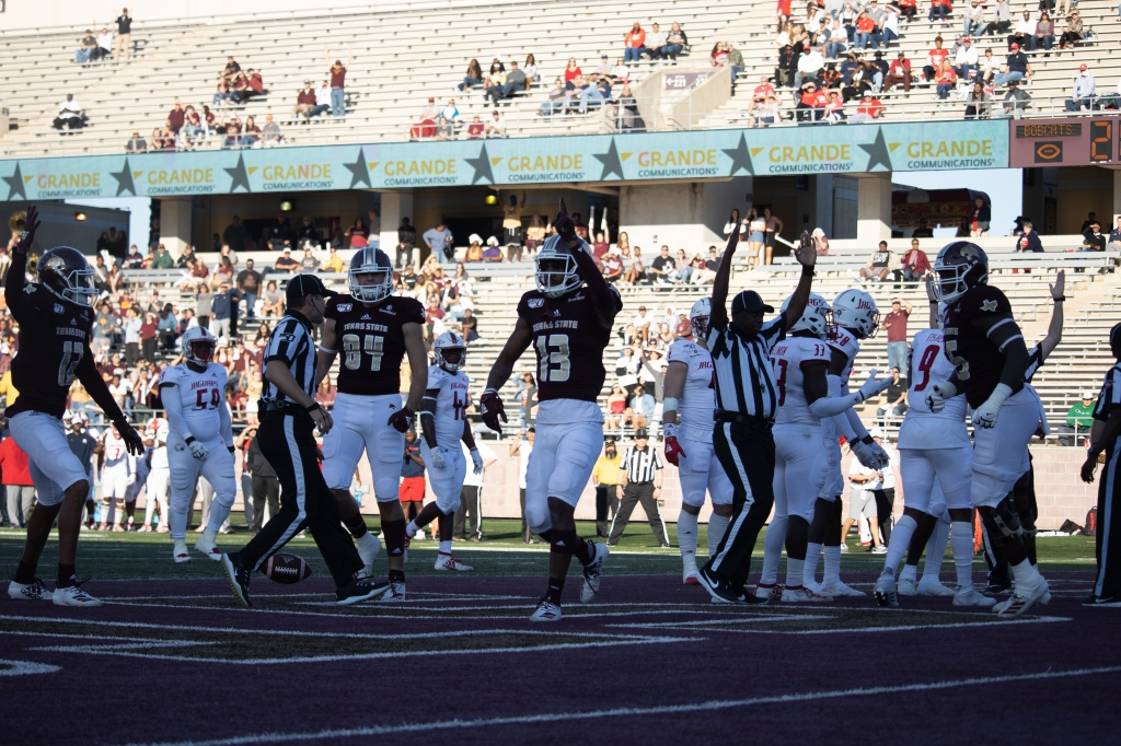 Trevis Graham is holding one finger in the air walking in the endzone after scoring his second touchdown of the game, while the referee signals a touchdown call. Javen Banks, Seth Caillouet and Aaron Brewer are all walking to meet up with Graham to celebrate.