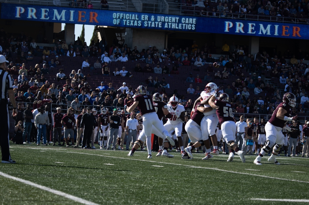 Tyler Vitt throws the ball from the pocket while South Alabama defenders are breaking through the offensive line. The Texas State sideline and fans are in the background of the photo.