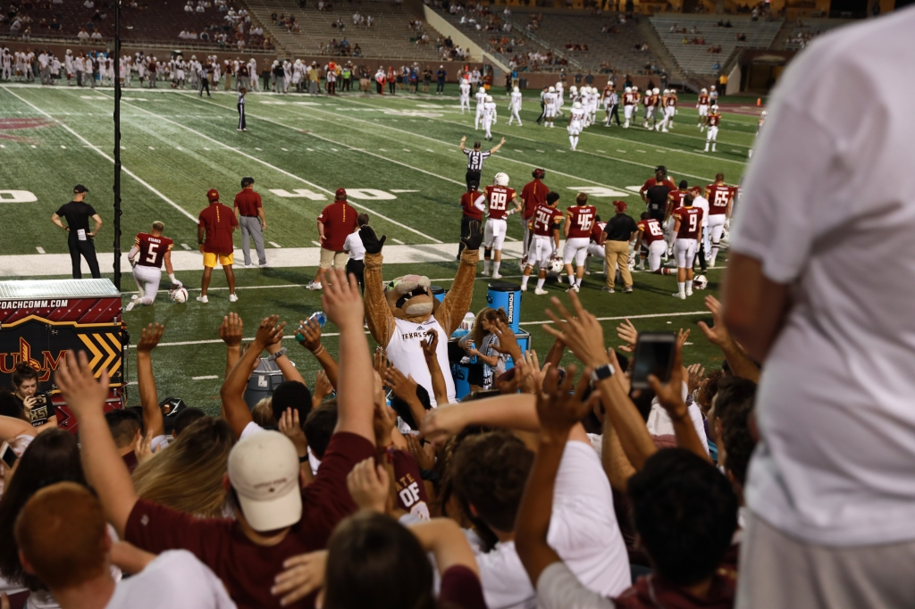 Boko, Texas State's mascot is raising his hands high in front of the student section that's located behind the opposing team's bench. The ULM football team are focused on the game on the field while ULM and Texas State battle inside the Warhawk side of the field.