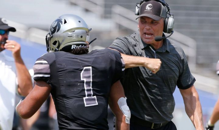 Head coach John Walsh with a headset and dark grey polo gets excited and elbow bumps his player on their way to the sidelines during a Denton Guyer football game.