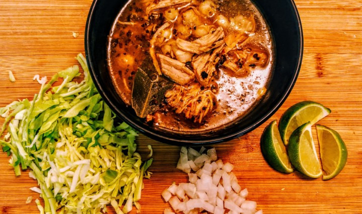 Limes, Onions,Lettuce, Chicken all placed around and in a black bowl on a brown wood table.