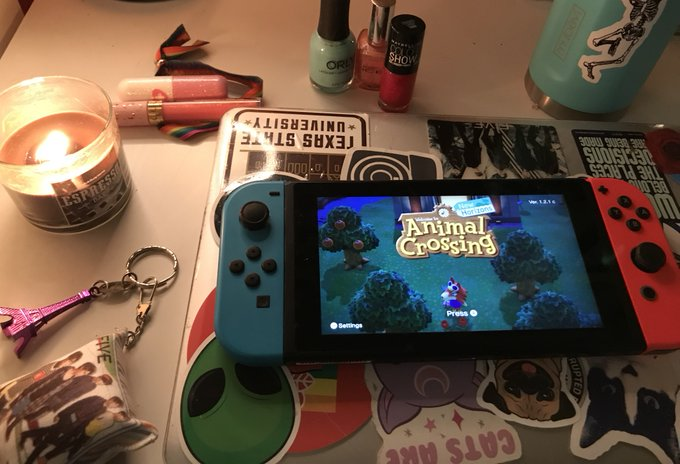 "Image of Nintendo Switch on desk, surrounded by different objects with ""Animal Crossing"" on screen."