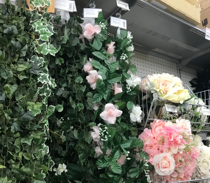 Image of faux pink roses on green vine surrounded by other fake flowers at Michaels.