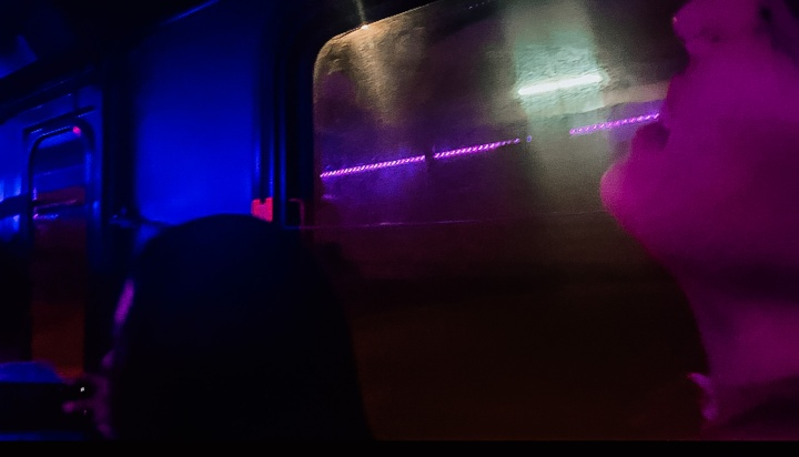 people aboard a bus in colorful lighting
