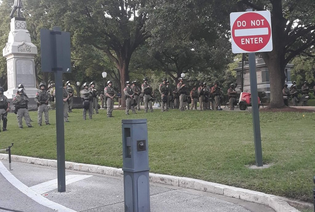 Police officers in military clothing stand lined up in downtown Austin Capitol Park in the middle of a protest.