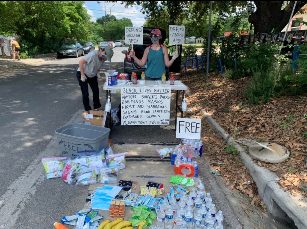 Photo of a stand with free water, snacks, and sunscreen at the protest