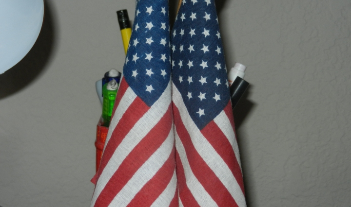 Two mini American flags sit in a pencil holder.