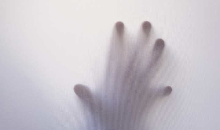 Photo of a foggy glass wall with a hand