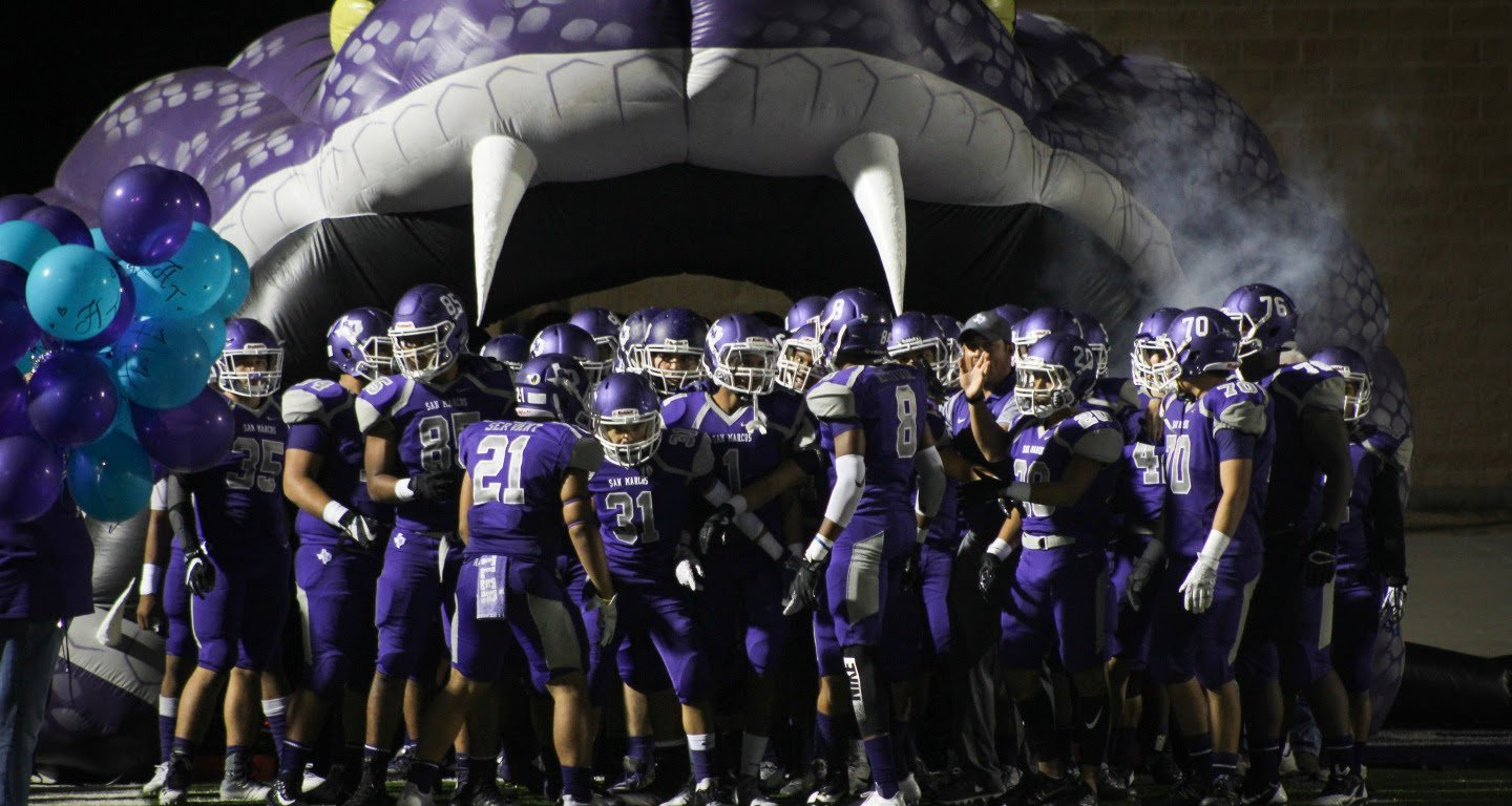 San Marcos HS football players walk into the field at Toyota Rattler Stadium through a giant purple snake entryway before kickoff.