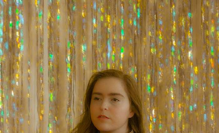 The album cover is a portrait of a young female in front of iridescent streamers.