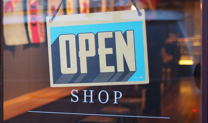 "An ""open"" sign in block lettering on the front of a shop door."