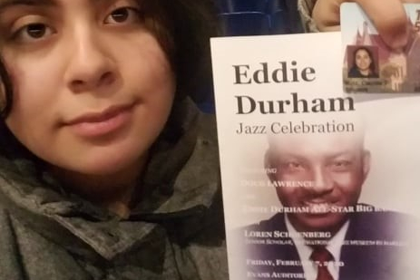 The self-portrait is taken of the author of this article. The author is posing with a 'Eddie Durham Jazz Celebration' concert flyer that showcases a graphic image of Eddie Durhan on the cover; the author took this picture while posing in front of the Evans Auditorium stage, post-concert.