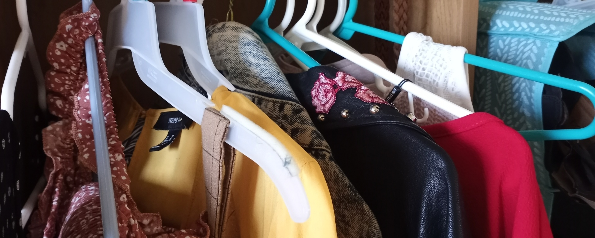 Variety of clothes hanging on clothing hangers