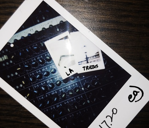 "The album cover for ""LA Trains"" by eaJ Alt-text: There is a polaroid of the soundboard with two blurred out polaroids sitting on top of it. The two polaroids have LA Trains written on them in sharpie. And the larger polaroid has the date 01.17.20 and eaJ written on it in sharpie."