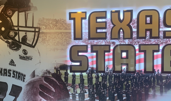 Picture is of a Texas State mural on a wall with a football player holding a ball and the stadium with the band on the field in the background.