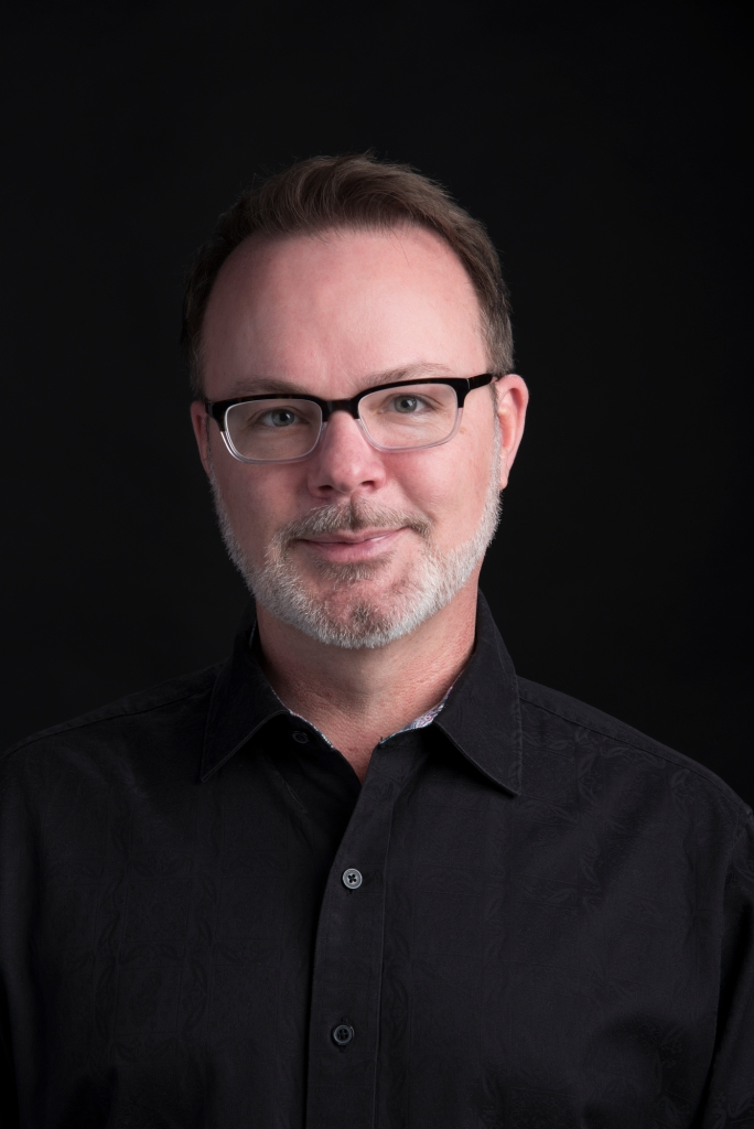 A portrait image of Texas State University's School of Music director, Dr. Joey Martin. Black background with a man wearing a solid black shirt and thick-rimmed glasses stares directly at you.