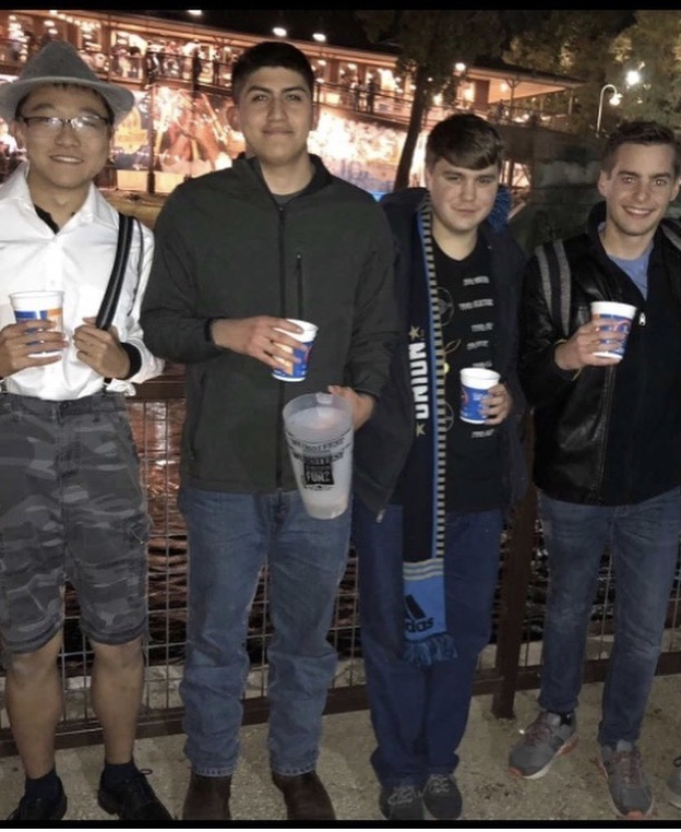 four men stand side by side of each other holding cups