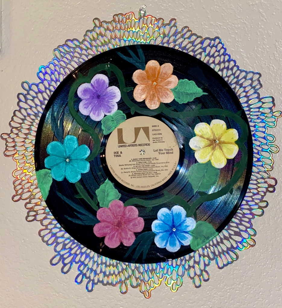 Painted flowers on vinyl record, glued on top of the iridescent placemat