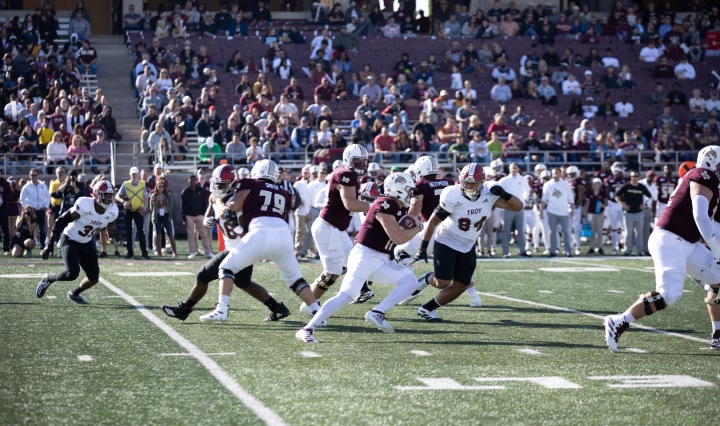 Texas State quarterback Tyler Vitt scrambles versus Troy. He is holding the ball as Troy players move in to make the tackle.