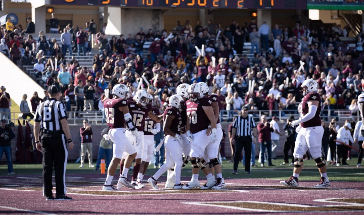 Several Texas State Bobcat football players celebrate after scoring on 2019 senior day