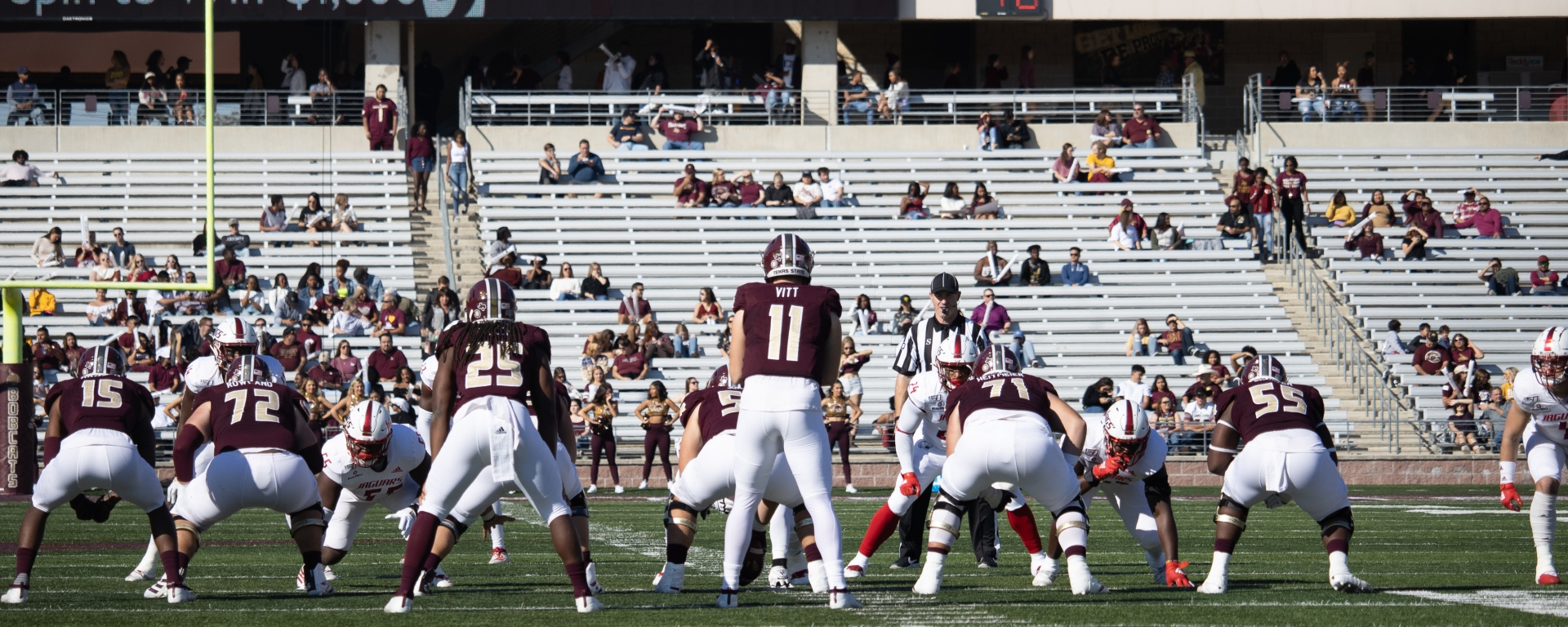 Texas State quarterback Tyler Vitt awaits the snap. His offensive line is in front of him and running back is to his left.