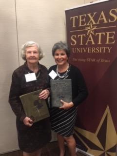 Gloria Campos and Gene Yates holding Southwest Texas State yearbooks.