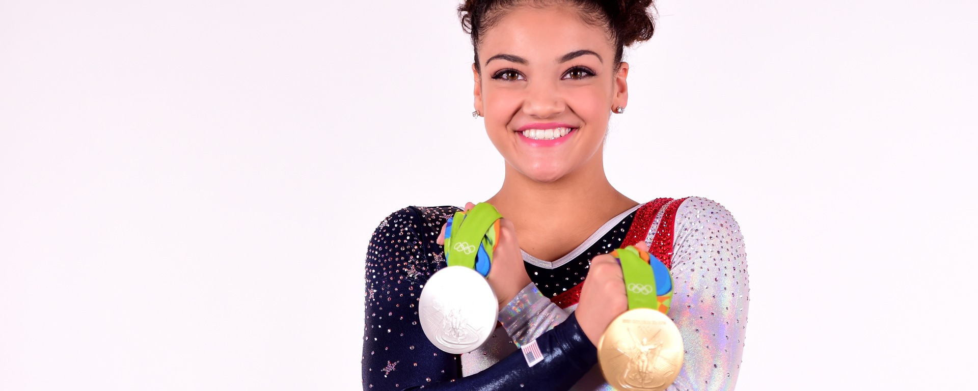 Laurie Hernandez poses in her team USA gymnastics leotard while holding a gold and silver medal.
