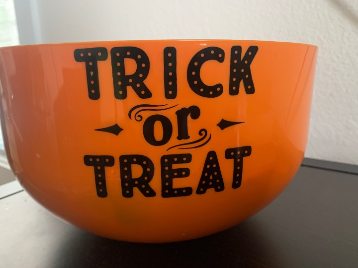 An orange bucket that says trick or treats on the side