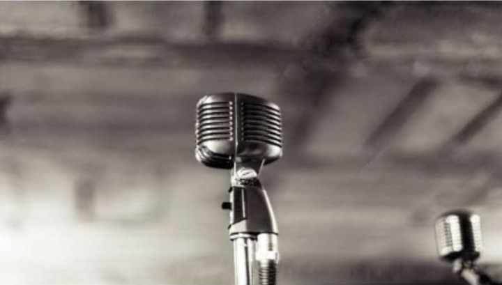Black and White photo of a vocal microphone, with the background out of focus, and a slightly smaller microphone to the right.