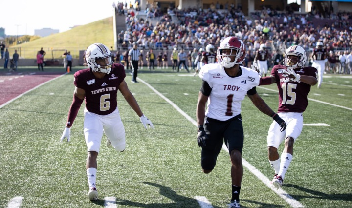 Texas State is playing Troy in their 2019 matchup. There are two Bobcat defenders. One is on each side of the Troy player.