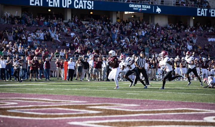 Texas State is playing Troy in their 2019 matchup. A Texas State player is running into the endzone pursued by a Troy defender.