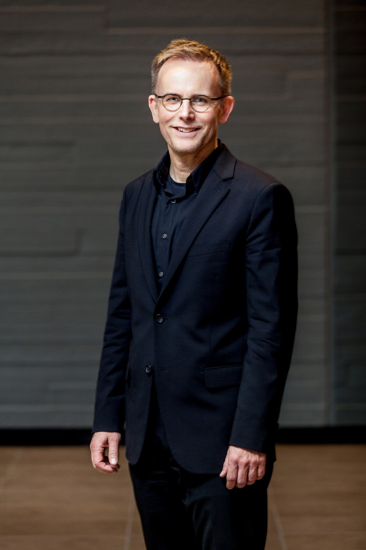 A portrait image of Texas State University's School of Music Artist-in-Residence, Dr. Craig Hella Johnson. A man wearing a solid black suit and circular-glasses smiles at the camera.