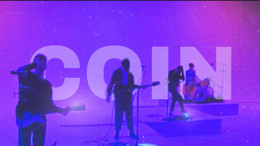"COIN under purple and blue lights with ""COIN"" typed behind them"