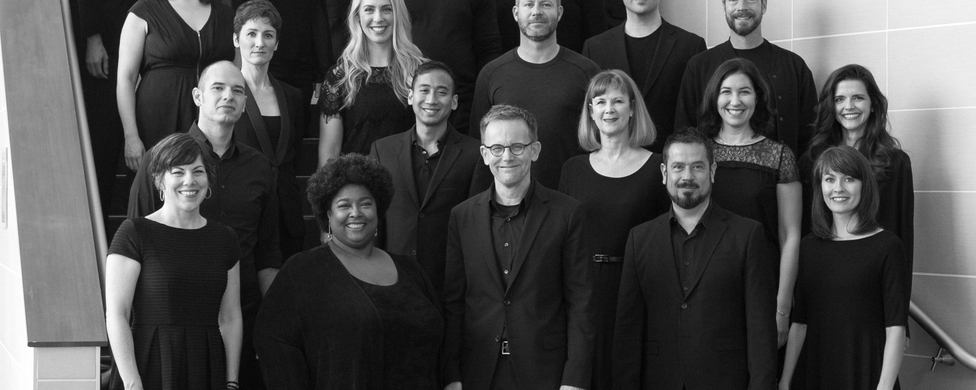A black-and-white group shot image taken of members of the ensemble Conspirare that performed Dr. Johnson's piece, Considering Matthew Shepard. Multiple people with black evening attire are posing and smiling, center-fold.
