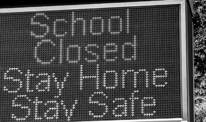 "A Black and White picture of a billboard with the words: ""Schools Closed, Stay Home Stay Safe"" written. There is a tree in the background."