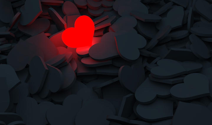 one bright red heart surrounded by black hearts