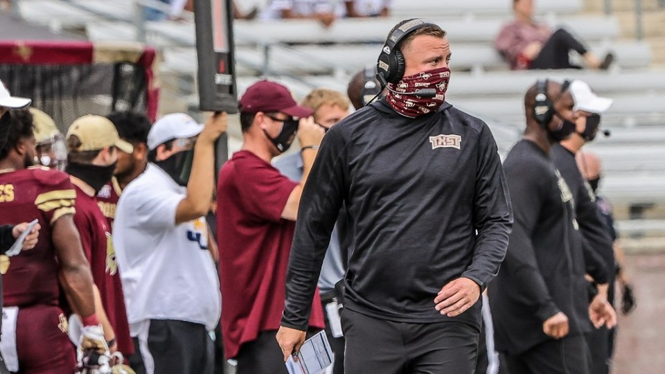 Texas State Head Coach Jake Spavital is walking down the sideline. He is looking onto the field.