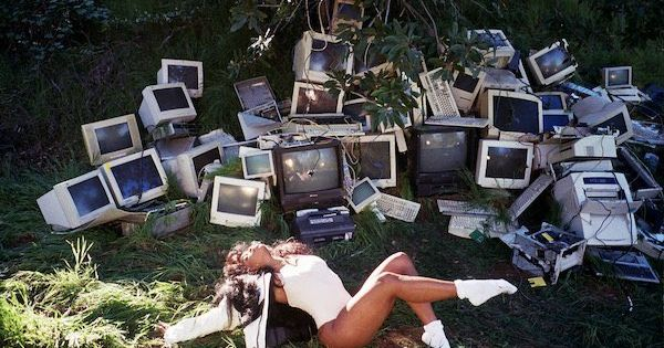 """Album art of """"CTRL"""" with SZA in a field of busted computers and greenery, bathing in the sunlit."""