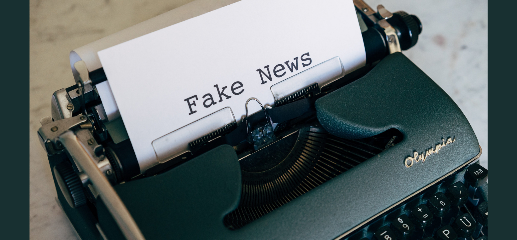 an image of a typewriter and a paper that says fake news placed against a dark background