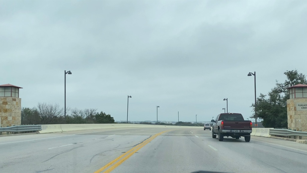 Image of Purgatory Creek Bridge with cars driving over.